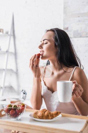 Photo pour Jeune femme brune mangeant de la fraise pour le petit déjeuner au lit - image libre de droit