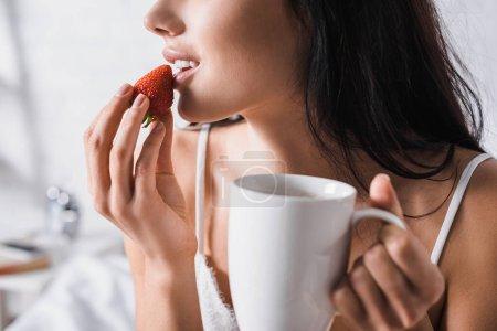 abgeschnittene Ansicht einer jungen brünetten Frau mit Becher, die Erdbeere zum Frühstück isst