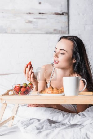 young brunette woman having croissant and strawberry for breakfast and drinking cocoa in bed