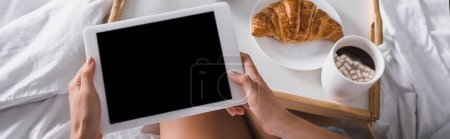 cropped view of woman having croissant and cocoa for breakfast while holding digital tablet in bed, banner