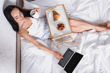 junge brünette Frau frühstückt im Bett, während sie Laptop benutzt