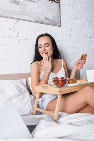 smiling young brunette woman having breakfast in bed while watching movie on laptop
