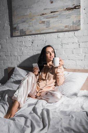 junge brünette Frau sitzt morgens mit Becher und Smartphone im Bett