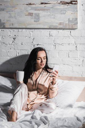 Photo for Young brunette woman sitting in bed with mug and smartphone at morning - Royalty Free Image