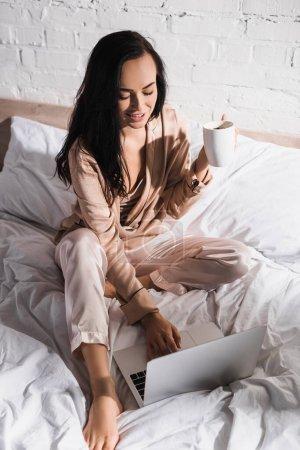 jeune femme brune assise au lit avec tasse et ordinateur portable le matin