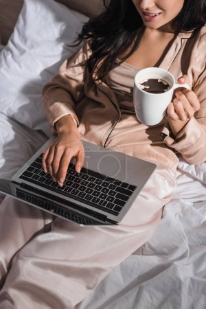 Photo for Cropped view of young brunette woman sitting in bed with mug and laptop at morning - Royalty Free Image
