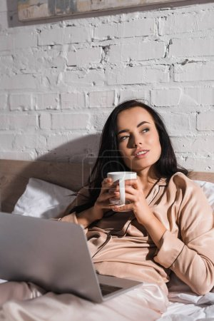 Photo for Young brunette woman sitting in bed with mug and laptop at morning - Royalty Free Image