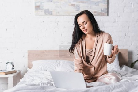 young brunette woman sitting in bed with mug and laptop at morning