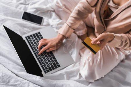 vue recadrée de la femme assise au lit avec smartphone, carte de crédit et ordinateur portable le matin
