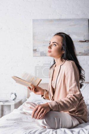 Photo pour Rêveuse jeune femme brune assise au lit avec livre le matin - image libre de droit
