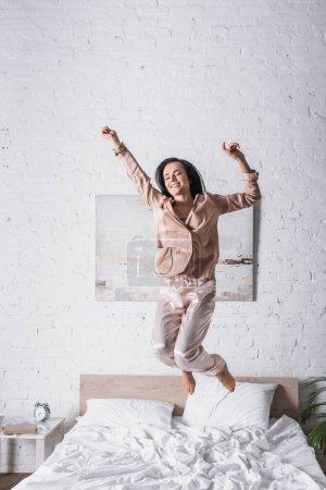 Photo pour Jeune femme brune sautant au lit le matin - image libre de droit