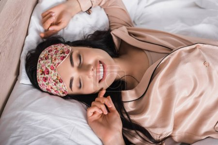 top view of smiling young brunette woman lying in bed in sleep mask