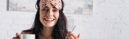 Lächelnde junge brünette Frau in Schlafmaske mit Kakaobecher und Smartphone, Banner