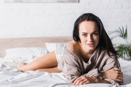 Photo for Young brunette woman in sweater and socks lying in bed at morning - Royalty Free Image