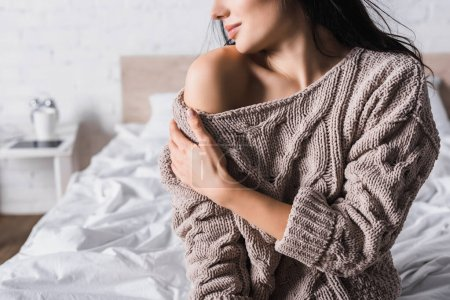 Photo for Cropped view of young brunette woman in sweater with bare shoulder sitting in bed at morning - Royalty Free Image