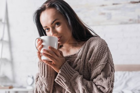 Photo for Young brunette woman in sweater sitting in bed with mug of hot cocoa at morning - Royalty Free Image