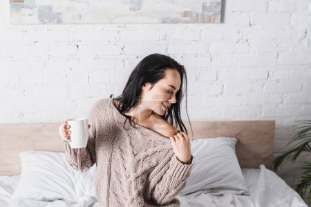 Photo for Young brunette woman in sweater with bare shoulder sitting in bed with mug of hot cocoa at morning - Royalty Free Image