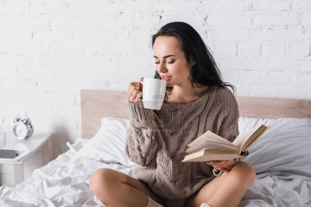 young brunette woman in sweater sitting in bed with mug of hot cocoa and book at morning