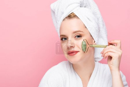 Photo for Young woman in bathrobe with towel on head using jade roller isolated on pink - Royalty Free Image