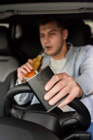 junger Mann hält Flasche in der Hand und trinkt Whiskey während der Autofahrt, verschwommener Hintergrund