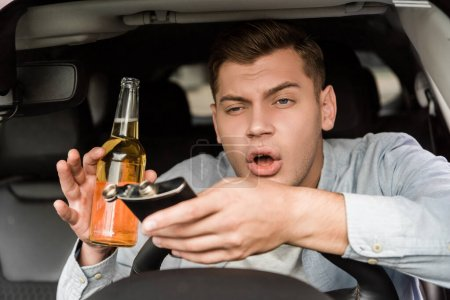 drunk man holding bottle of whiskey and flask while sitting in car