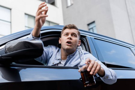 Photo for Drunk, angry man with bottle of whiskey shouting while looking out car window - Royalty Free Image
