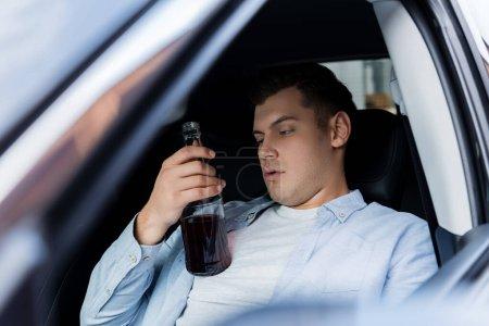 Photo pour Homme ivre tenant bouteille de whisky tout en étant assis sur le siège du conducteur dans la voiture - image libre de droit