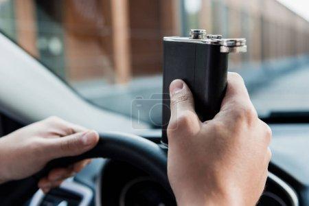 Photo pour Vue recadrée de l'homme tenant la fiole avec de l'alcool tout en conduisant la voiture, fond flou - image libre de droit