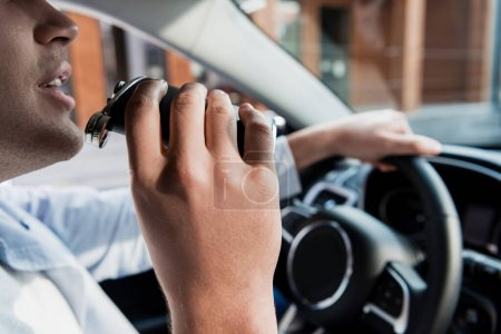 cropped view of man drinking alcohol from flask while driving car, blurred background