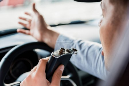 Photo pour Vue recadrée de l'homme gesticulant et tenant une fiole avec de l'alcool pendant qu'il conduisait une voiture, avant-plan flou - image libre de droit