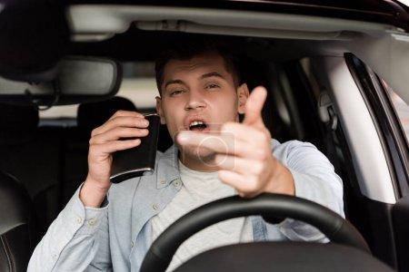 Betrunkener hält Flasche mit Alkohol und zeigt Mittelfinger im Auto, verschwommener Vordergrund