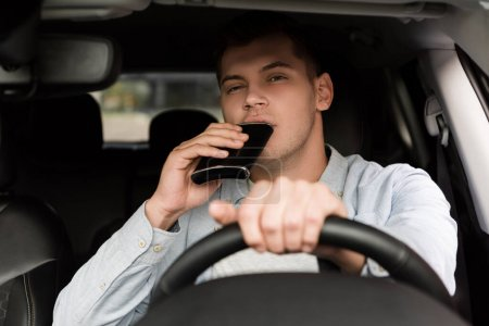young man drinking alcohol from flask while driving car, blurred foreground