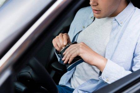 Teilansicht von Mann, der Flasche mit Alkohol öffnet, während er im Auto auf verschwommenem Vordergrund sitzt