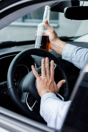 partial view of man beeping while driving car and holding bottle of whiskey, blurred foreground