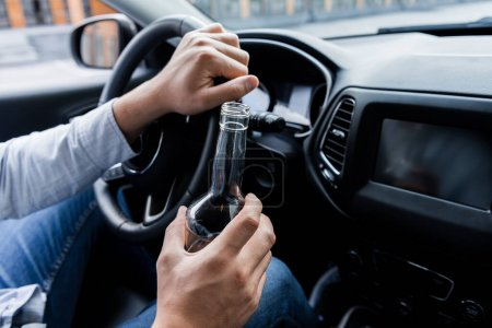 Photo for Partial view of man holding bottle of whiskey while driving car - Royalty Free Image