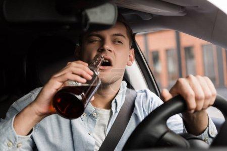 Photo pour Homme ivre conduisant une voiture et buvant du whisky au premier plan flou - image libre de droit