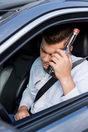 Betrunkener sitzt mit geschlossenen Augen im Auto und hält Flasche Whiskey am Kopf, verschwommener Vordergrund