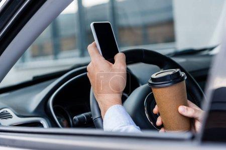 Photo pour Vue partielle de l'homme tenant du café pour aller et bavarder sur smartphone en voiture au premier plan flou - image libre de droit
