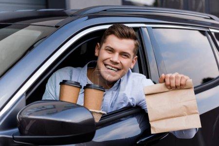 Photo pour Conducteur joyeux tenant café pour aller et sac en papier tout en souriant à la caméra - image libre de droit