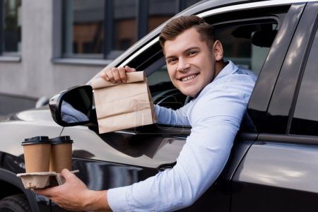 happy man holding disposable cups and paper bag while sitting in car and looking at camera