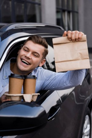 happy man holding disposable cup and paper bag while sitting in car
