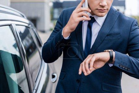 Photo pour Vue recadrée de l'homme d'affaires regardant montre-bracelet tout en parlant sur smartphone près de la voiture - image libre de droit