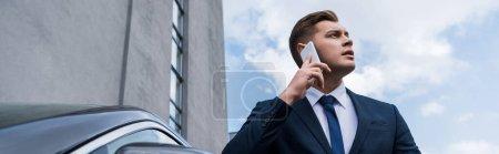 junger Geschäftsmann schaut weg, während er im Freien mit dem Smartphone spricht, Banner