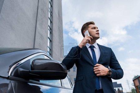 Foto de Joven hombre de negocios hablando en el teléfono móvil cerca de coche en primer plano borrosa - Imagen libre de derechos