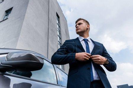 Photo pour Faible angle de vue de l'homme d'affaires boutonnage blazer près de la voiture - image libre de droit