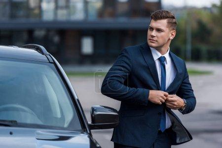 Photo pour Homme d'affaires boutonnage blazer près de la voiture, flou au premier plan - image libre de droit
