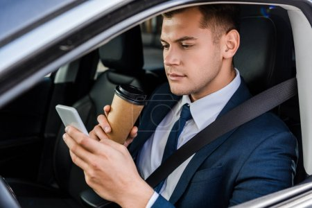 Young businessman using smartphone and holding coffee to go on driver seat in car