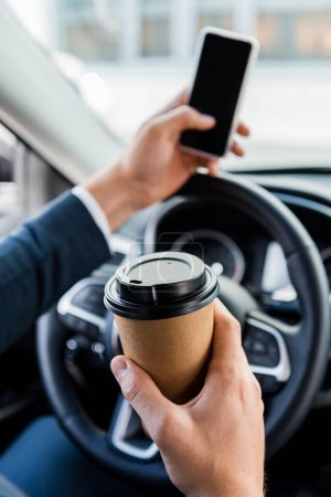 Photo for Cropped view of businessman holding coffee to go and smartphone on blurred background in car - Royalty Free Image
