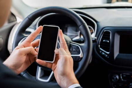 Photo for Cropped view of man holding smartphone with blank screen near steering wheel in car on blurred background - Royalty Free Image