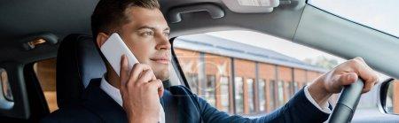 Junger Geschäftsmann im Anzug fährt Auto und spricht auf Smartphone, Banner
